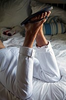 legs of young man in flip_flops laying on bed