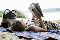 Germany, Rheinland, Young woman lying on blanket and reading book