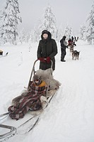 Mother with son having dog_sled ride, Kakslauttanen, Ivalo, Lapland, Finnland