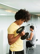 Black man using dumbbells in gym