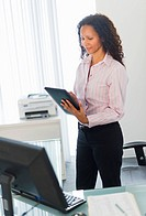Hispanic businesswoman using digital tablet in office