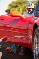 Smiling Man Sitting in Red Sports Car With Door Open, Hawaii, USA