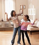 African American grandmother and granddaughter dancing in living room