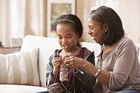 African American grandmother teaching granddaughter how to knit