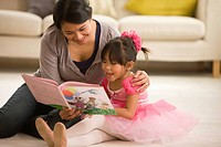 Asian mother reading book to daughter