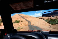 View of Remote Road Across Red Rocks Through Jeep Window, Moab, Utah, USA