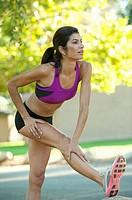 Hispanic woman in sportswear stretching in park