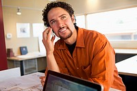 Mixed race businessman talking on cell phone in office