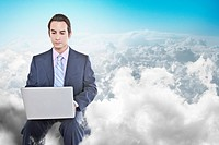 Mixed race businessman using laptop in clouds