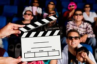 Clapperboard in front of Hispanic people in movie theater