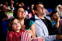 Hispanic family watching film in movie theater