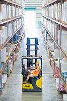 Worker sitting on forklift in warehouse