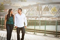 Hispanic couple walking on urban bridge