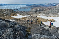 Group of hikers with a guide, icebergs near Tiniteqilaaq, Ammassalik Peninsula, at Sermilik Fjord, East Greenland, Greenland