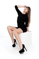 Young woman posing confidently in a short black dress with high heels