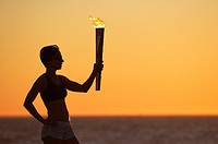 Silhouette portrait of a woman on the beach with a simulated Olympics relay torch