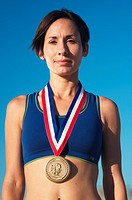Portrait of a woman on the beach with a simulated Olympic gold medal