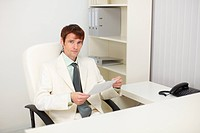 Young businessman sits in the study