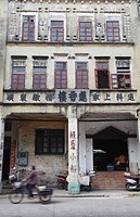 Woman cycling past crumbling colonial architecture, Chikanzhen, Guangdong, Guangdong, China, Asia