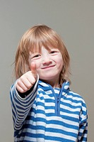boy with long blond hair showing thumbs up sign, smiling _ isolated on gray