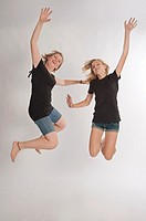 Two teenage girls Central European and jumping during a photo shoot
