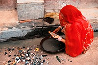 Woman looking for gold dust in a sewer in India