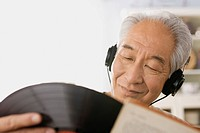 Senior man listening to vinyl record