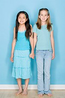 Studio shot portrait of two teenage girls holding hands, full length