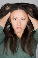 Studio portrait of stressed Chinese woman