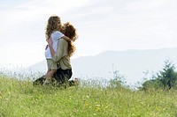 Mother and daughter embracing in meadow