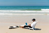 A Businessman Sits On A Beach Chair On The Beach Working On A Laptop Computer With His Surfboard Sitting At His Feet, Tarifa Cadiz Andalusia Spain