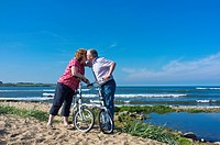 A Man And Woman Exchange A Kiss While On A Bike Ride Along The Water, Northumberland England