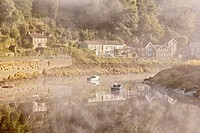 View of village on riverbank in mist at dawn, Tintern, River Wye, Wye Valley, Monmouthshire, Wales, august