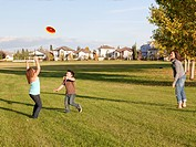mother throwing flying disc to children in a park, beaumont alberta canada