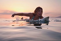 a woman paddling on a surfboard at sunset, tarifa cadiz andalusia spain