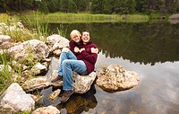 a couple sitting on a rock at the water´s edge in laughter, black hills south dakota united states of america