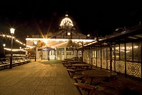 tables and chairs in a walkway and a building at the pier illuminated at night, eastbourne sussex england
