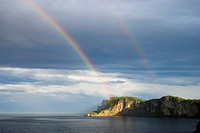 double rainbow on a seaside cliff, quebec canada
