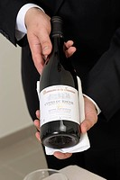 Wine waiter presenting a bottle of red wine before decantering