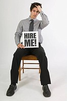 Frustrated man holding a hire me! sign