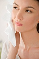 Woman taking off makeup with facial tissue