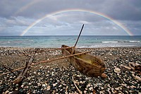 Vanuatu, Penama Province, Pentecost Island, Pangi, dugout canoe on a pebble beach and rainbow over the sea