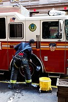 United States, New York City, Manhattan, fireman cleaning a fire truck