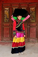 Yi tribal woman in traditional clothes at her house, Lijiang, Yunnan, China