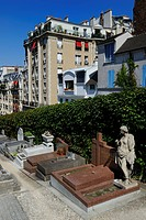 France, Paris, Butte Montmartre, Saint Vincent cemetery surrounded by buildings and the grave of the painter Utrillo