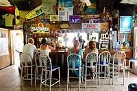 Bahamas, Grand Bahama Island, Freeport, Port Lucaya, Rum Runners Bar, customers sit at the counter of a rum bar