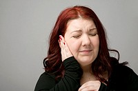 A auburn haired caucasian woman suffering from earache pain in the ear