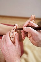 Traditional Thai foot massage with wooden stick