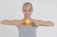 Young woman holding a yellow spiky massage ball between her index fingers