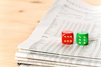 Red and green dice on a newspaper with stock prices